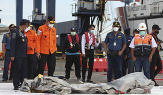 Rescuers inspects found in the waters around the location where a Sriwijaya Air passenger jet has lost contact with air traffic controllers shortly after the takeoff, at the search and rescue command center at Tanjung Priok Port in Jakarta, Indonesia, Sunday, Jan. 10, 2021. The Boeing 737-500 took off from Jakarta for Pontianak, the capital of West Kalimantan province on Indonesia's Borneo island, and lost contact with the control tower a few moments later. (AP Photo/Achmad Ibrahim)