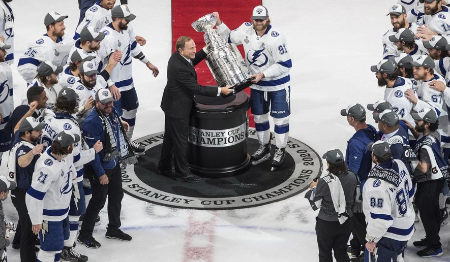 FILE - In this Sept. 28, 2020, file photo, Tampa Bay Lightning's Steven Stamkos (91) is presented the Stanley Cup from NHL commissioner Gary Bettman as they celebrate after defeating the Dallas Stars in the NHL Stanley Cup hockey finals in Edmonton, Alberta. The NHL is embarking on a 56-game regular season with all divisional play in a knock-down, drag-out battle for the Stanley Cup unlike any other in hockey history.  (Jason Franson/The Canadian Press via AP, File)