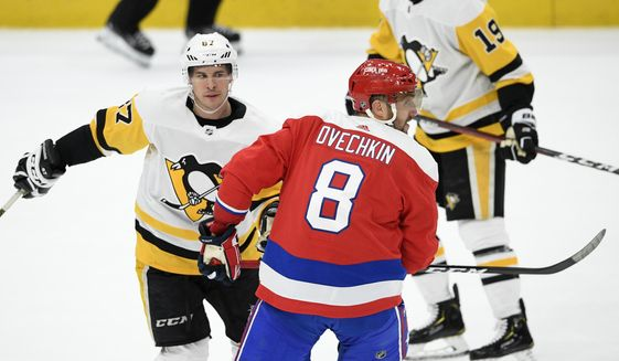 In this Feb. 2, 2020, file photo, Washington Capitals left wing Alex Ovechkin (8), of Russia, skates next to Pittsburgh Penguins center Sidney Crosby (87) during the third period of an NHL hockey game in Washington. The NHL is embarking on a 56-game regular season with all divisional play in a knock-down, drag-out battle for the Stanley Cup unlike any other in hockey history.  (AP Photo/Nick Wass, File) **FILE**