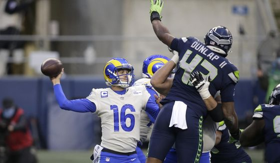 Seattle Seahawks defensive end Carlos Dunlap (43) leaps to try and deflect a pass from Los Angeles Rams quarterback Jared Goff during the second half of an NFL wild-card playoff football game, Saturday, Jan. 9, 2021, in Seattle. (AP Photo/Scott Eklund)