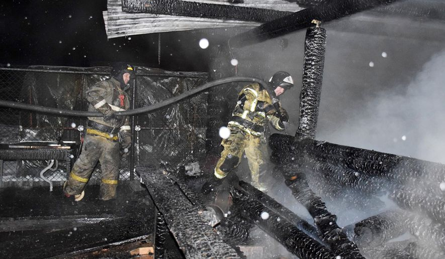 In this photo released by Russian Emergency Ministry Press Service, firefighters work at the site of fire at a nursing home in the town of Borovsky, western Siberia, Russia, Saturday, Jan. 9, 2021. Russian authorities say seven people have died in the fire at a nursing home in western Siberia. The fire that broke out Saturday at the private home for the elderly also injured a resident, according to Russia's top criminal investigation agency. (Russian Ministry of Emergency Situations press service via AP)