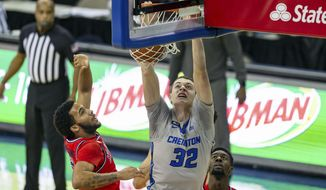 Creighton center Ryan Kalkbrenner (32) makes a dunk against St. John's guard Julian Champagnie (2) in the first half during an NCAA college basketball game, Saturday, Jan. 9, 2021, in Omaha, Neb. (AP Photo/John Peterson)