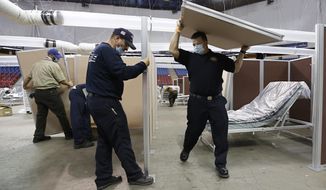 FILE — In this April 18, 2020 file photo partitions are installed between beds as work is performed to turn Sleep Train Arena into a 400-bed emergency field hospital to help deal with the coronavirus, in Sacramento, Calif. The state has reopened the arena and other facilities to help handle a new surge of coronavirus patients, but is using little more than a handful of volunteers from Gov. Gavin Newsom's California Health Corps who originally helped staff the facility. (AP Photo/Rich Pedroncelli, File)