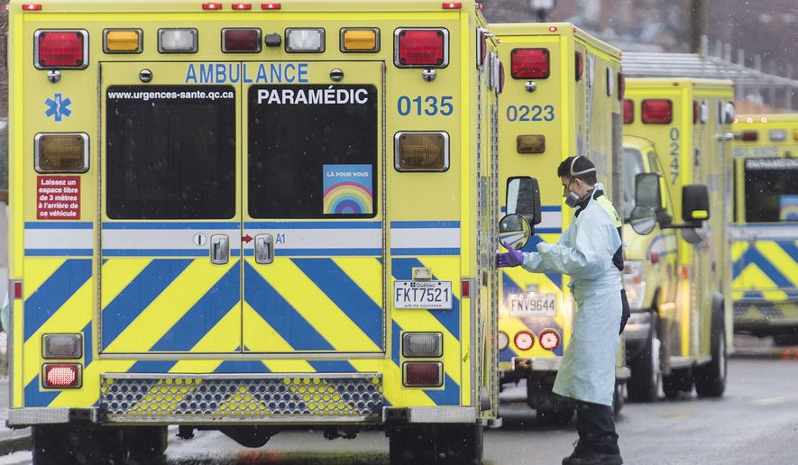 A paramedic is shown next to an ambulance outside a hospital in Montreal, Monday, Dec. 28, 2020, as the COVID-19 pandemic continues in Canada and around the world. (Graham Hughes/The Canadian Press via AP)