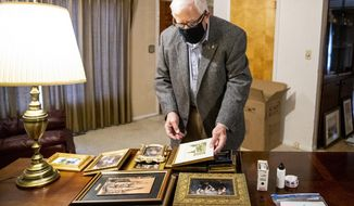 Recently retired Wyoming U.S. Sen. Mike Enzi sorts through photographs in his new Gillette, Wyoming, office on Tuesday, Dec. 22, 2020. (Mike Moore/Gillette News Record via AP)