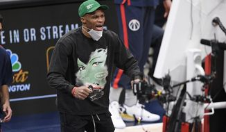 Washington Wizards guard Russell Westbrook reacts in street clothes as he watches during the first half of an NBA basketball game against the Miami Heat, Saturday, Jan. 9, 2021, in Washington. (AP Photo/Nick Wass)