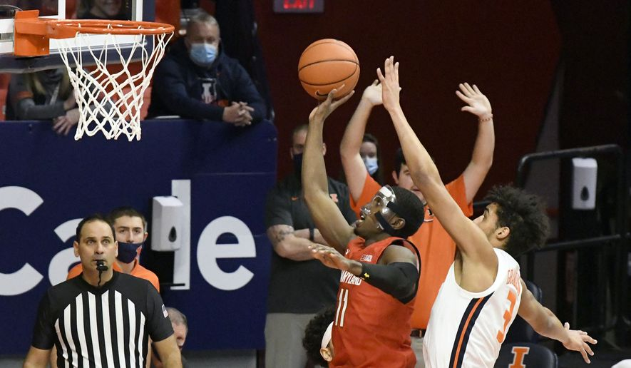 Maryland guard Darryl Morsell (11) shoots as Illinois guard Jacob Grandison (3) defends in the first half of an NCAA college basketball game, Sunday, Jan. 10, 2021, in Champaign, Ill. (AP Photo/Holly Hart)
