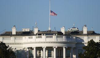 An American flag flies at half-staff above the White House in Washington, Sunday, Jan. 10, 2021. (AP Photo/Patrick Semansky)