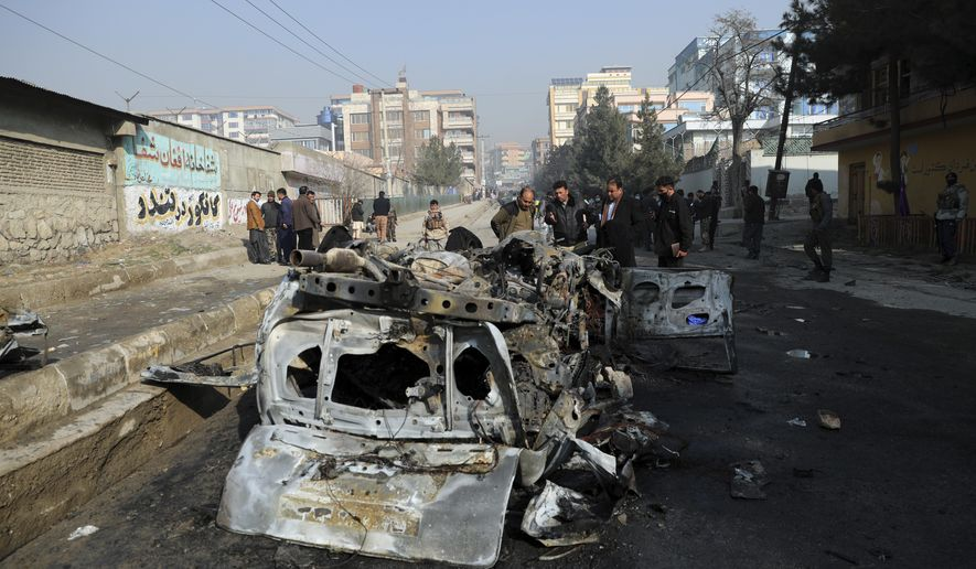 Afghan security officers inspect the site of a bomb attack in Kabul, Afghanistan, Sunday, Jan. 10, 2021. A roadside bomb exploded in Afghanistan's capital Sunday, killing at least a few people in a vehicle, the latest attack to take place even as government negotiators are in Qatar to resume peace talks with the Taliban. (AP Photo/Rahmat Gul)