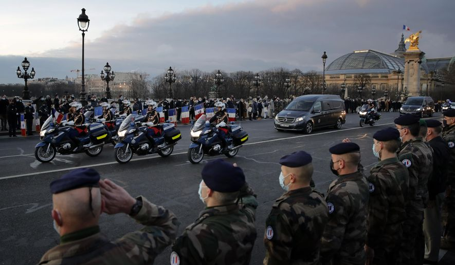 French soldiers stand in an honour guard on Thursday Jan.7, 2021 as the hearse convoy of late French forces soldiers rides on the Alexandre III bridge in central Paris. A ceremony was held to pay homage to two soldiers killed in Mali by an improvised explosive device that hit their armored vehicle on Saturday. Three other French soldiers died just five days earlier in similar circumstances . (AP Photo/Christophe Ena)
