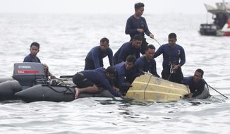 Indonesian Navy divers pull out a part of an airplane out of the water during a search operation for the Sriwijaya Air passenger jet that crashed into the sea near Jakarta, Indonesia, Sunday, Jan. 10, 2021. Indonesian divers on Sunday located parts of the wreckage of the Boeing 737-500 in the Java Sea, a day after the aircraft with dozens of people onboard crashed shortly after takeoff from Jakarta. (AP Photo/Achmad Ibrahim)