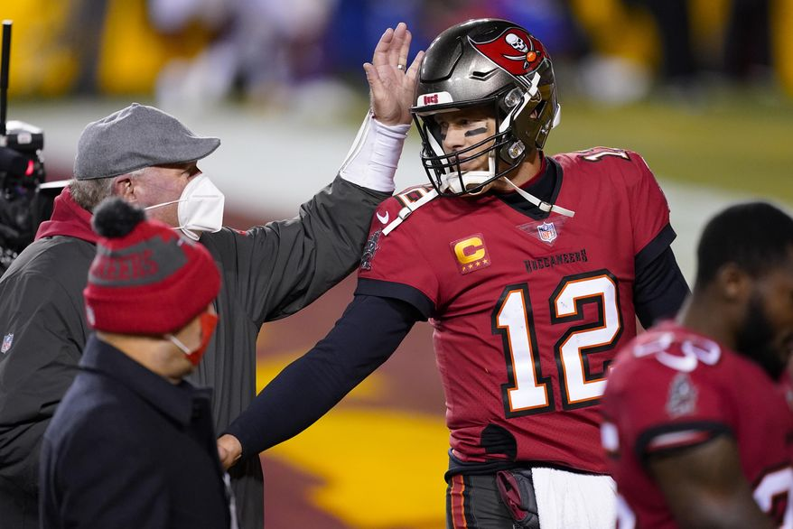 Tampa Bay Buccaneers head coach Bruce Arians, left, pats quarterback Tom Brady's helmet at the end an NFL wild-card playoff football game against the Washington Football Team, Saturday, Jan. 9, 2021, in Landover, Md. Tampa Bay won 31-23. (AP Photo/Andrew Harnik) **FILE**