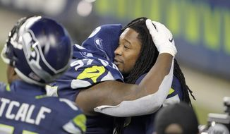 Seattle Seahawks' Shaquill Griffin, right, embraces teammate Poona Ford after the team lost to the Los Angeles Rams in an NFL wild-card playoff football game, Saturday, Jan. 9, 2021, in Seattle. (AP Photo/Ted S. Warren)