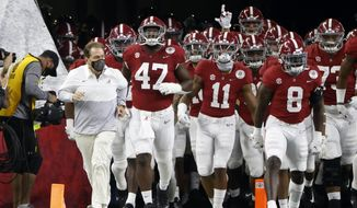 Alabama head coach Nick Saban, front left, jogs onto the field with his team for their Rose Bowl NCAA college football game against Notre Dame in Arlington, Texas, Friday, Jan. 1, 2021. (AP Photo/Ron Jenkins) **FILE**