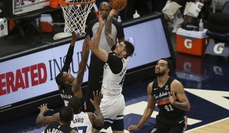Minnesota Timberwolves' Juancho Hernangomez (41) shoots the ball over San Antonio Spurs' Dejounte Murray (5) in the first half of an NBA basketball game Sunday, Jan. 10, 2021, in Minneapolis. (AP Photo/Stacy Bengs)