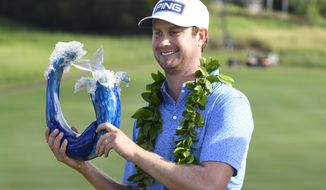 Harris English holds the champions trophy after the final round of the Tournament of Champions golf event, Sunday, Jan. 10, 2021, at Kapalua Plantation Course in Kapalua, Hawaii. (Matthew Thayer/The Maui News via AP)