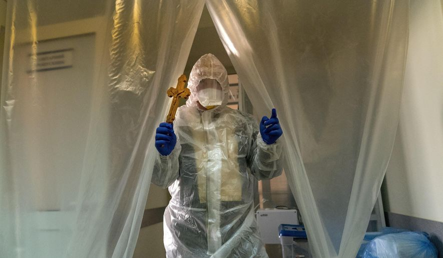 Father Stephan, Ukrainian Greek Catholic Church priest, wearing a special suit to protect himself against coronavirus enters an intensive care unit of the emergency hospital to visit visiting patients with COVID-19 in Lviv, Western Ukraine, Saturday, Jan. 9, 2021.  (AP Photo/Evgeniy Maloletka)