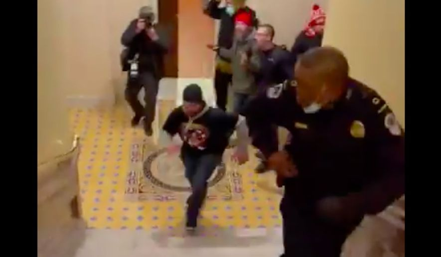 Capitol Police officer Eugene Goodman is being hailed a hero after a now-viral video showed him luring an angry mob of Trump supporters away from the Senate floor during Wednesday's violent insurrection at the U.S. Capitol. (Screengrab via Twitter/@igorbobic)