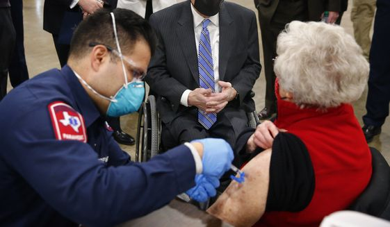 Texas Governor Greg Abbott (center) visits with Barbara Alexander of Bedford as she receives her COVID-19 shot from Arlington firefighter Andrew Harris at a mass vaccination site inside the Esports Stadium Arlington & Expo Center in Arlington, Texas, Monday, January 11, 2021. Alongside local and state officials, Abbott provided an update on COVID-19 vaccine efforts in Texas. (Tom Fox/The Dallas Morning News via AP, Pool)