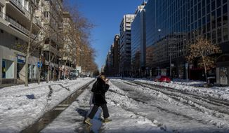 A woman walks through the snow in Madrid, Spain, Monday, Jan. 11, 2021. The Spanish capital is trying to get back on its feet after a 50-year record snowfall that paralyzed large parts of central Spain over the weekend. (AP Photo/Manu Fernandez)