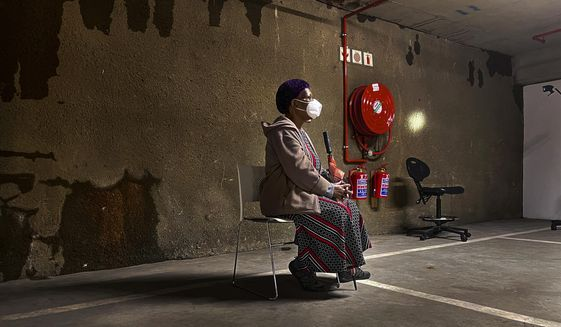 A lone woman waits to be tested for COVID-19 in the parking garage of a shopping mall in Johannesburg, South Africa, Monday Jan. 11, 2021. South Africa is struggling to cope with a spike in COVID-19 cases that has already overwhelmed some hospitals, as people returning from widespread holiday travel speed the country's more infectious coronavirus variant. (AP Photo/Jerome Delay)