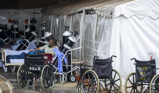 A patient wearing an oxygen mask is treated in a makeshift emergency unit at Steve Biko Academic Hospital in Pretoria, South Africa, Monday, Jan. 11, 2021, which is battling an ever-increasing number of Covid-19 patients. (AP Photo/Themba Hadebe)