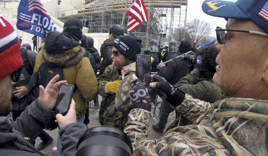 Trump supporters use cell phones to make images of a man injured during a protest with police, Wednesday, Jan. 6, 2021, at the Capitol in Washington. (AP Photo/Julio Cortez)