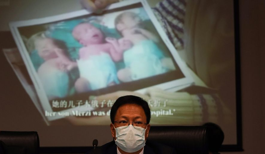"Xu Guixiang, a deputy spokesperson for the Xinjiang regional government, looks up near a slide showing a photo of Uighur infants during a press conference to refute accusations of genocide in Beijing, China. The Chinese official on Monday denied Beijing has imposed coercive birth control measures among Muslim minority women, following an outcry over a tweet by the Chinese Embassy in Washington claiming that government polices had freed women of the Uighur ethnic group from being ""baby-making machines."" (AP Photo/Ng Han Guan)"