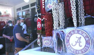 CORRECTS YEAR TO 2021 INSTEAD OF 2020 - Football fans shop for souvenirs, Sunday, Jan. 10, 2021, in Miami Beach, Fla. Ohio State, and Alabama will play the College Football Playoff National Championship game in Miami Gardens on Monday night. (AP Photo/Marta Lavandier)