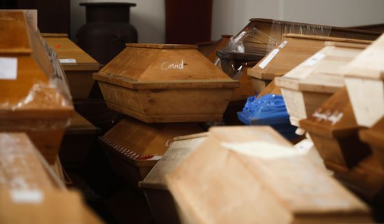 """Coffins containing deceased people wait in the worship room of the crematorium in Meissen, Germany, before cremation on Monday, Jan. 11, 2021. For those who died with the coronavirus, the coffins are marked with the word """"COVID"""" as a warning. (AP Photo/Markus Schreiber)"""