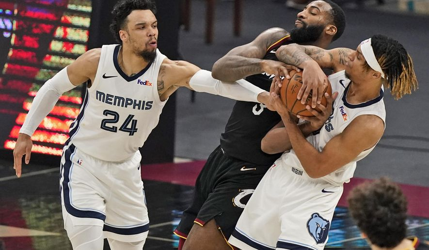 Cleveland Cavaliers' Andre Drummond, center, battles for the ball with Memphis Grizzlies' Dillon Brooks, left, and Brandon Clarke in the second half of an NBA basketball game, Monday, Jan. 11, 2021, in Cleveland. (AP Photo/Tony Dejak)