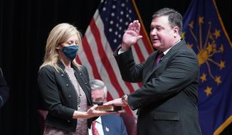 Todd Rokita is sworn in as Indiana's attorney general by Chief Justice Loretta H. Rush on a bible held by his wife, Kathy, during an inaugural ceremony at the Indiana State Museum, Monday, Jan. 11, 2021, in Indianapolis. (AP Photo/Darron Cummings)