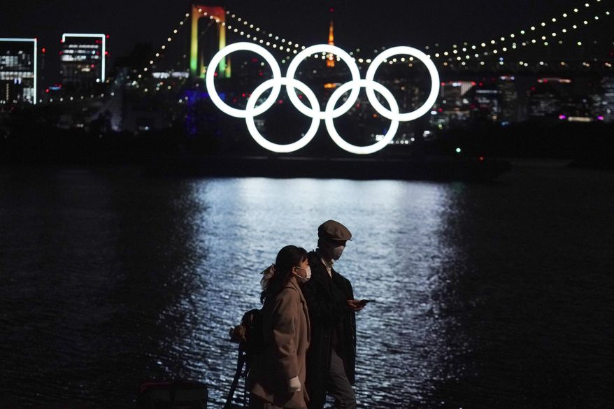In this Dec. 1, 2020, file photo, a man and a woman walk past near the Olympic rings floating in the water in the Odaiba section in Tokyo. More than 80% of people in Japan who were surveyed in two polls in the last few days say the Tokyo Olympics should be canceled or postponed, or say they believe the Olympics will not take place. (AP Photo/Eugene Hoshiko, File)