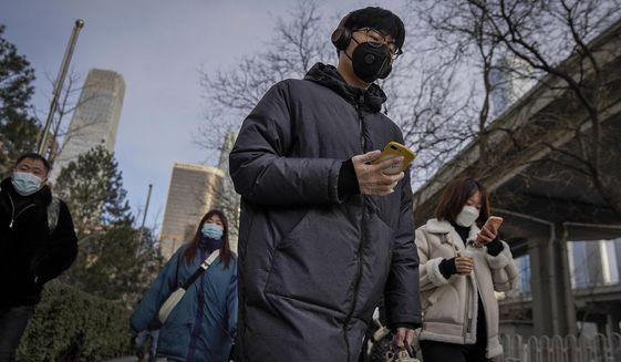 A man wearing a face mask and a disposable gloves to help curb the spread of the coronavirus heads to work with other masked people during the morning rush hour in Beijing, Monday, Jan. 11, 2012. Chinese health authorities say scores more people have tested positive for coronavirus in Hebei province bordering on the capital Beijing. The outbreak focused on the Hebei cities of Shijiazhuang and Xingtai is one of China's most serious in recent months and comes amid measures to curb the further spread during next month's Lunar New Year holiday. (AP Photo/Andy Wong)