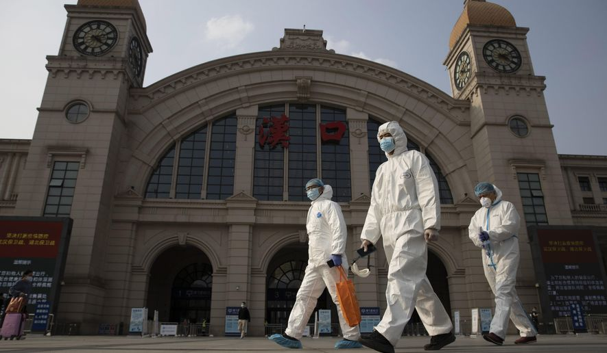 FILE - In this April 7, 2020, file photo, workers in protective suits walk past the Hankou railway station on the eve of its resuming outbound traffic in Wuhan in central China's Hubei province. China says a group of experts from the World Health Organization are due to arrive Thursday, Jan. 14, 2021, for an investigation into the origins of the coronavirus pandemic. A one-sentence announcement from the National Health Commission on Monday, Jan. 11, said the experts would be meeting with Chinese counterparts but gave no other details.(AP Photo/Ng Han Guan, File)