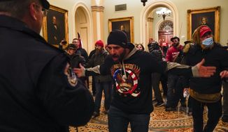 Rioters gesture to U.S. Capitol Police in the hallway outside of the Senate chamber at the Capitol in Washington, Wednesday, Jan. 6, 2021, near the Ohio Clock. (AP Photo/Manuel Balce Ceneta)  **FILE**