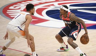 Washington Wizards guard Bradley Beal (3) dribbles the ball against Phoenix Suns guard Devin Booker (1) during the second half of an NBA basketball game, Monday, Jan. 11, 2021, in Washington. (AP Photo/Nick Wass) **FILE**