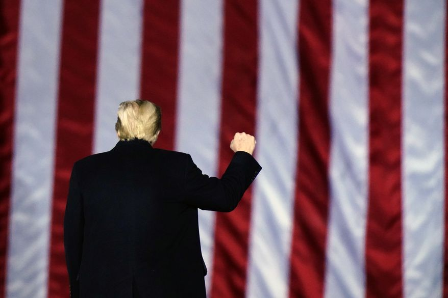 In this Monday, Jan. 4, 2021, file photo, President Donald Trump gestures at a campaign rally in support of Senate candidates Sen. Kelly Loeffler, R-Ga., and David Perdue in Dalton, Ga. (AP Photo/Brynn Anderson, File)