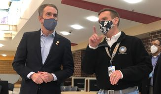 Dr. Stephen Haering (right), health director for the city of Alexandria, gives Virginia Gov. Ralph Northam a walkthrough of a coronavirus vaccine distribution center as the city began phase 1B of its rollout on Tuesday. (Gabriella Muñoz/The Washington Times)