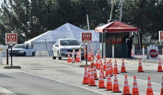 COVID-19 vaccination tents are set up in the north of the Toy Story parking lot at the Disneyland Resort on Tuesday, Jan. 12, 2021, in Anaheim, Calif. The parking lot is located off Katella Avenue and sits southeast of Disneyland. (Jeff Gritchen/The Orange County Register via AP)