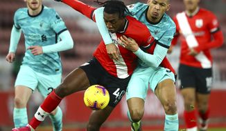 Southampton's San Nlundulu, left, and Liverpool's Fabinho battle for the ball during the English Premier League soccer match between Southampton and Liverpool at St Mary's Stadium, Southampton, England, Monday, Jan. 4, 2021. (AP Photo/Michael Steele,Pool)