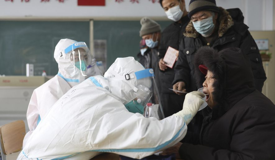 In this photo released by China's Xinhua News Agency, workers in protective suits take a swab for a coronavirus test in Shenyang in northeastern China's Liaoning Province, Monday, Jan. 11, 2021. Lockdowns have been expanded and a major political conference postponed in a province next to Beijing that is the scene of China's most serious recent COVID-19 outbreak. (Yao Jianfeng/Xinhua via AP)