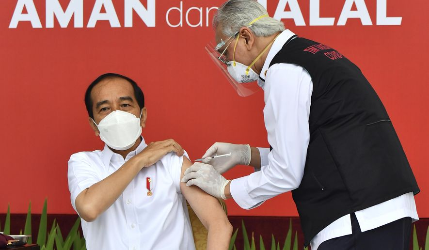 "In this photo released by Indonesian Presidential Palace, President Joko Widodo, left, receives a shot of COVID-19 vaccine at Merdeka Palace in Jakarta, Indonesia, Wednesday, Jan. 13, 2021. Widodo on Wednesday received the first shot of a Chinese-made COVID-19 vaccine after Indonesia approved it for emergency use and began efforts to vaccine millions of people in the world's fourth most populated country. Writings on the banner in the background read ""Safe and Halal."" (Agus Suparto/Indonesian Presidential Palace via AP)"
