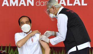 """In this photo released by Indonesian Presidential Palace, President Joko Widodo, left, receives a shot of COVID-19 vaccine at Merdeka Palace in Jakarta, Indonesia, Wednesday, Jan. 13, 2021. Widodo on Wednesday received the first shot of a Chinese-made COVID-19 vaccine after Indonesia approved it for emergency use and began efforts to vaccine millions of people in the world's fourth most populated country. Writings on the banner in the background read """"Safe and Halal."""" (Agus Suparto/Indonesian Presidential Palace via AP)"""