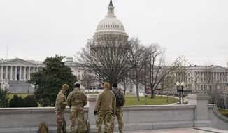 With the U.S. Capitol Building in view, members of the military stand on the steps of the Library of Congress' Thomas Jefferson Building in Washington, Friday, Jan. 8, 2021, in response to supporters of President Donald Trump who stormed the Capitol. (AP Photo/Patrick Semansky)