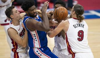 Philadelphia 76ers' Joel Embiid, center left, is defended by Miami Heat's Duncan Robinson, left, Chris Silva, center right, and Kelly Olynyk during the first half of an NBA basketball game Tuesday, Jan. 12, 2021, in Philadelphia. (AP Photo/Chris Szagola)