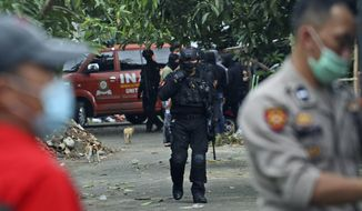 Police officers walk outside the site where two suspected militants were killed during a raid in Makassar, South Sulawesi, Indonesia, Wednesday, Jan. 6, 2021. Members of Indonesia's anti-terrorism police squad killed the two suspected militants who they believe were connected to a deadly suicide attack at a Roman Catholic cathedral in the southern Philippines, officials said. (AP Photo/Masyudi S. Firmansyah)