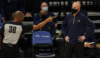 Indiana Pacers coach Nate Bjorkgren, right, watches as referee Michael Smith calls an offensive foul against the Pacers during the first half of an NBA basketball game against the Sacramento Kings in Sacramento, Calif., Monday, Jan. 11, 2021. (AP Photo/Rich Pedroncelli)