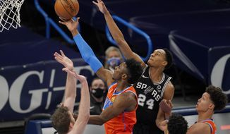 Oklahoma City Thunder guard Hamidou Diallo, center, goes to the basket between San Antonio Spurs center Jakob Poeltl, left, and guard Devin Vassell (24) during the first half of an NBA basketball game Tuesday, Jan. 12, 2021, in Oklahoma City. (AP Photo/Sue Ogrocki)