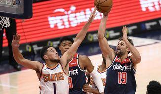 Washington Wizards guard Raul Neto (19) shoots against Phoenix Suns guard Devin Booker (1) during the second half of an NBA basketball game, Monday, Jan. 11, 2021, in Washington. (AP Photo/Nick Wass)